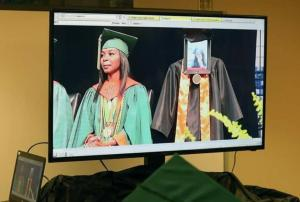 Family and friends gather to watch as iPad dressed in a cap and gown graduates